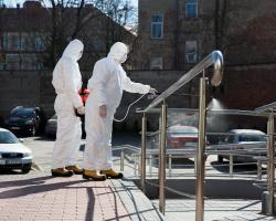 Strażacy z OSP w Podgórzu dezynfekują poręcze przed Urzędem Gminy w Łomży.