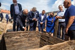 Poseł Lech Kołakowski sprawdza jakość odkopanego sprzed wieków drewna, podczas wizyty wicepremiera i ministra kultury i dziedzictwa narodowego Piotra Glińskiego na wykopaliskach archeologicznych na Starym Rynku w Łomży.