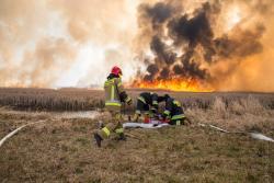 Goniądz, pożar Biebrzańskiego Parku Narodowego. Idzie ściana ognia. Strażacy uruchamiają pompę wodną, aby zasilić węże gaśnicze.