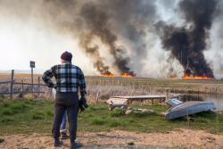 Wroceń, pożar Biebrzańskiego Parku Narodowego. W naprawdę szybkim tempie nadciąga ogień. Za chwile pojawią się strażacy, którzy będą polewać nadbrzeżną trawę, aby ogień nie przedostał się do zabudowań.