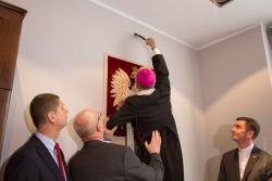 Bp Janusz Stepnowski zawiesza krzyż nad godłem podczas otwarcia biura senatora PIS Marka Komorowskiego