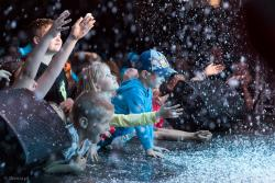 """Dzieci z niedowierzaniem dotykają śniegu w środku upalnego lata, dzięki iluzjonistycznemu pokazowi Macieja Pola oczywiście w ramach 32. Międzynarodowego Festiwalu Teatralnego """"Walizka""""."""