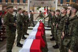 Wojskowy pogrzeb żołnierzy pochowanych pod przydrożnym krzyżem.
