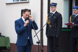Burmistrz Nowogrodu Grzegorz Palka ociera łzy po wspomnieniu śp. byłego burmistrza Józefa Piątka podczas przekazania samochodu strażackiego.