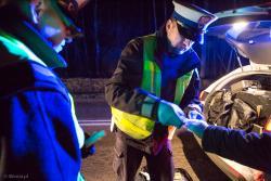 Policjanci opatrują poszkodowanego w zderzeniu z łosiem na DK 63 pod Podgórzem.