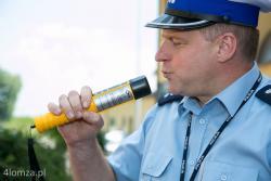 Nadkomisarz Piotr Pietrzak, naczelnik wydziału ruchu drogowego KMP w Łomży demonstruje jak dmuchać w urządzenie pomiarowe otrzymane od WORD Łomża