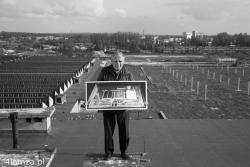 """Jerzy Pilski, budowniczy i pierwszy dyrektor łomżyńskiej """"Bawełny"""" stoi na dachu biurowca (obecnie WSA) ze zdjęciem makiety zakładu, w tle widać w miejscu hali produkcyjnej słupy Galerii Narew."""