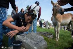 Uczniowie ze szkoły wyznaniowej w Sde Yaakov z Izraela razem ze swymi rówieśnikami z III LO w Łomży czarną farbą odświeżają napisy na macewach. Młody koń, pasący się niedaleko, zaciekawiony grupą osób, przyszedł to zobaczyć.