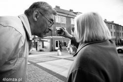 Fotograf Stanisław Andruszkiewicz zwraca uwagę pani robiącej zdjęcie pod słońce, ta jednak gasi fotografa mówiąc, że robi zdjęcia od czasu, gdy miała kilkanaście lat .