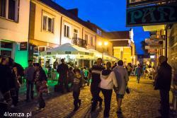 Ulica Farna wieczorem podczas Nocy Muzeów. Tłum, gwar i śpiewy. Miasto żyje.
