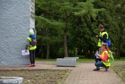 Chłopiec do pomiaru wykorzystuje swoją wysokość, aby przyśpieszyć obliczenie na jakiej wysokości powieszona jest tablica. Jego drużyna jest już w tyle. Wszystko odbywa się w ramach I Biegu Patrolowego Śladami Historii Łomży zorganizowanego przez Zespół Szkół Drzewnych i Gimnazjalnych w Łomży.