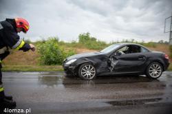 Strażak w deszczu fotografuje uszkodzone auto na drodze 647, w kierunku Śniadowa.