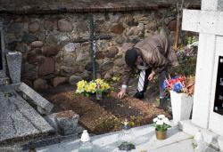 Mężczyzna w krawacie, w wyjściowym stroju sprząta, a raczej dopieszcza skromny grób przed dniem Wszystkich Świętych.