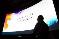 Właściciel kina Karol Charubin na tle zakrzywionego, srebrnego ekranu o rozmiarach 4 m x 9 m. Rusza Nowe Kino w Łomży