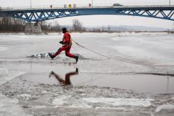 Ćwiczenia służb ratowniczych na plaży miejskiej, jak uratować człowieka tonącego na rzece skutej lodem.