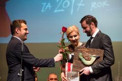 Reżyser Piotr Domalewski otrzymuje czerwoną różę od Prezydenta Mariusza Chrzanowskiego, a wiceprezydent, kobieta Agnieszka Muzyk obserwuje tę scenę podczas gali weręczania Nagród Prezydenta w dziedzinie Kultury za 2017 rok.