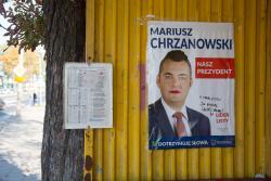 Plakat Mariusza Chrzanowskiego na przystanku autobusowym.